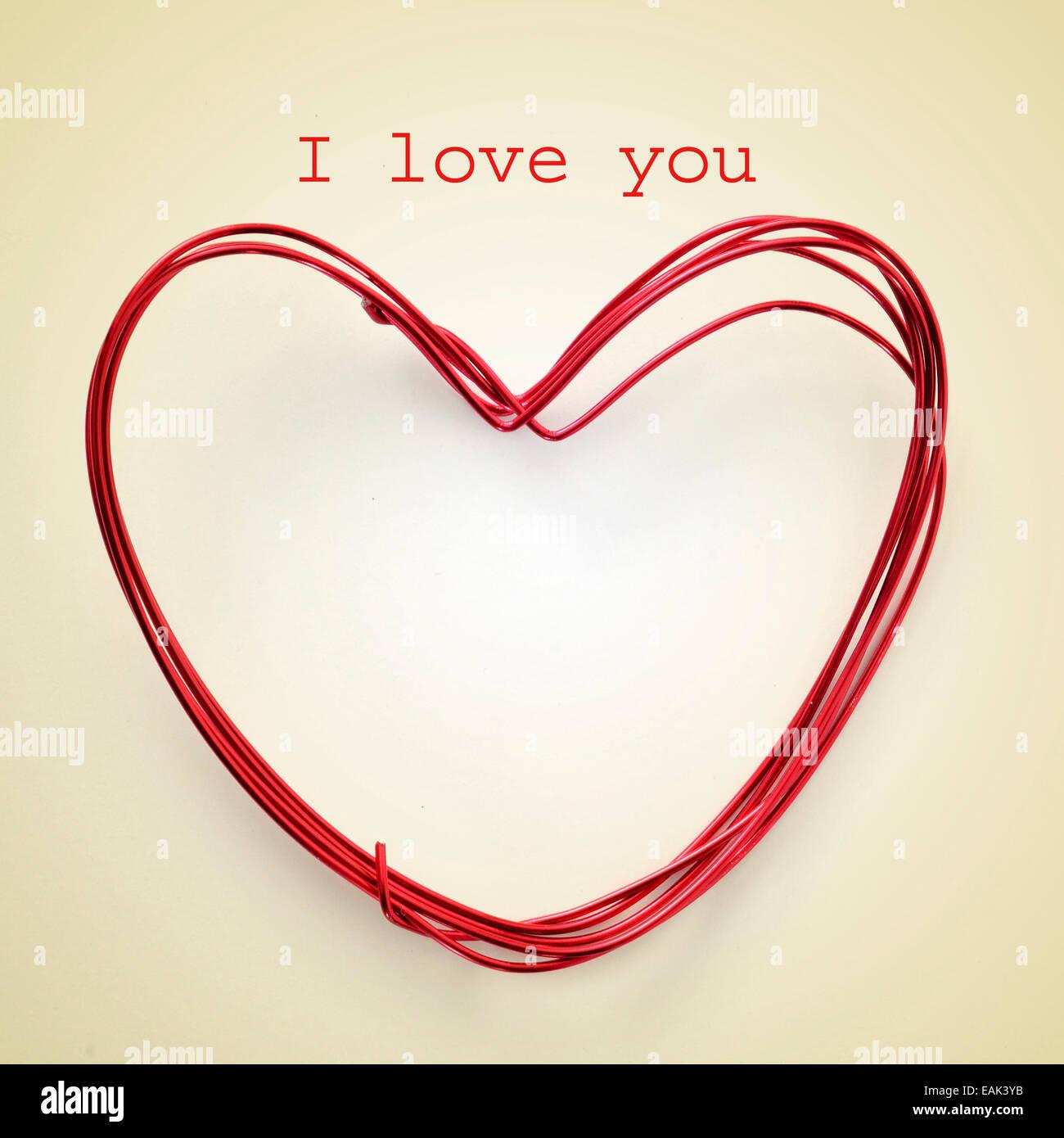 Frase ti amo e un cuore a forma di rotolo di filo su un sfondo beige, con un effetto retrò Foto Stock