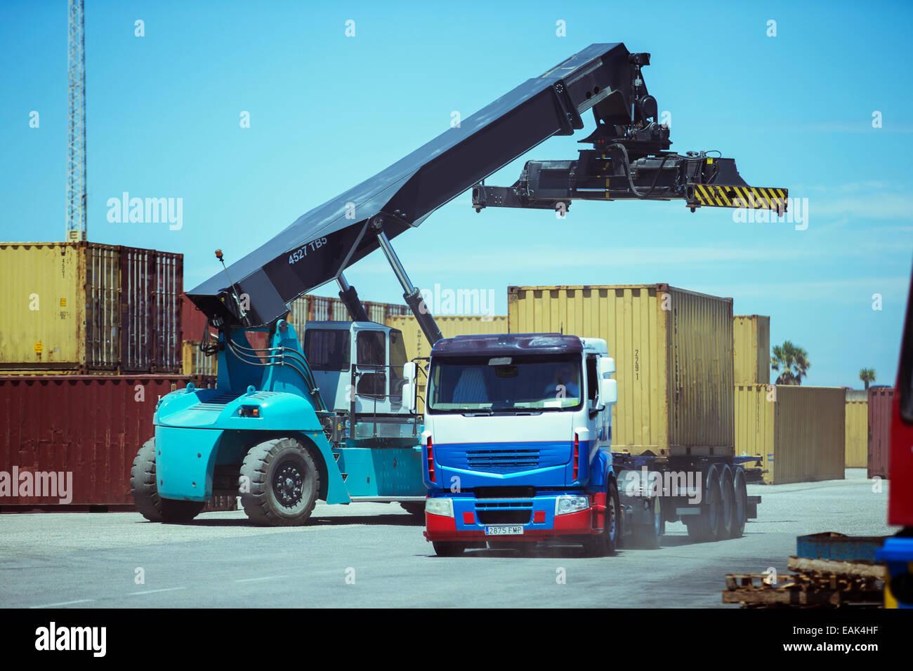 Gru vicino al contenitore di carico sul carrello Immagini Stock