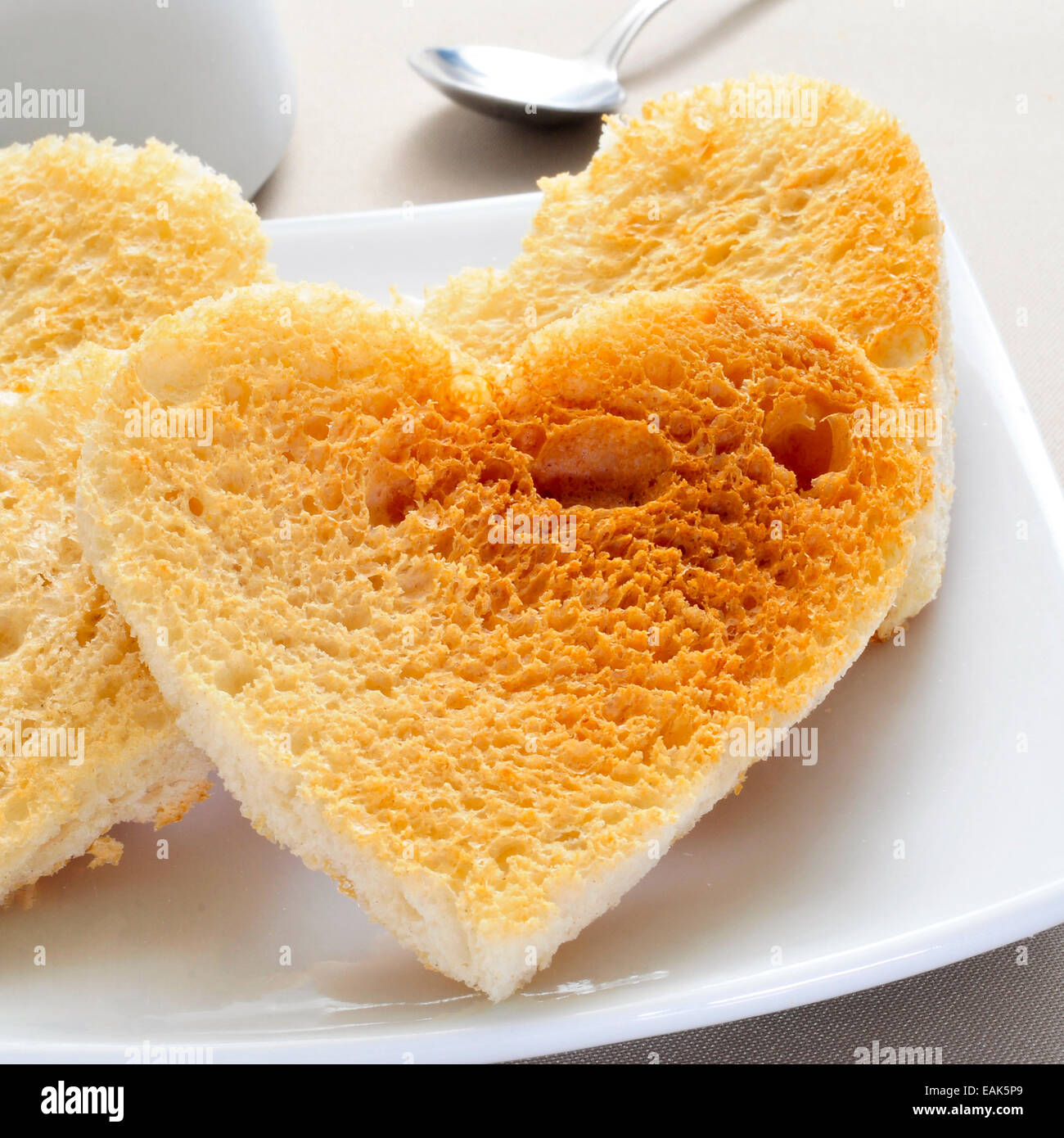 Una piastra con alcuni a forma di cuore toast servita su un set table Immagini Stock