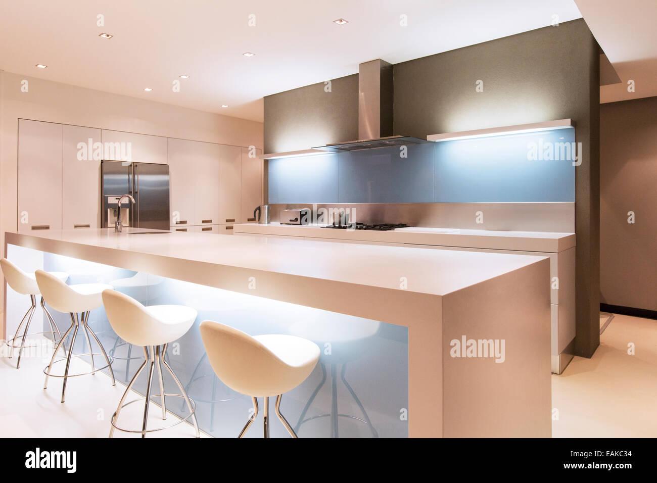 Bianca e moderna cucina con isola e sgabelli illuminata di notte
