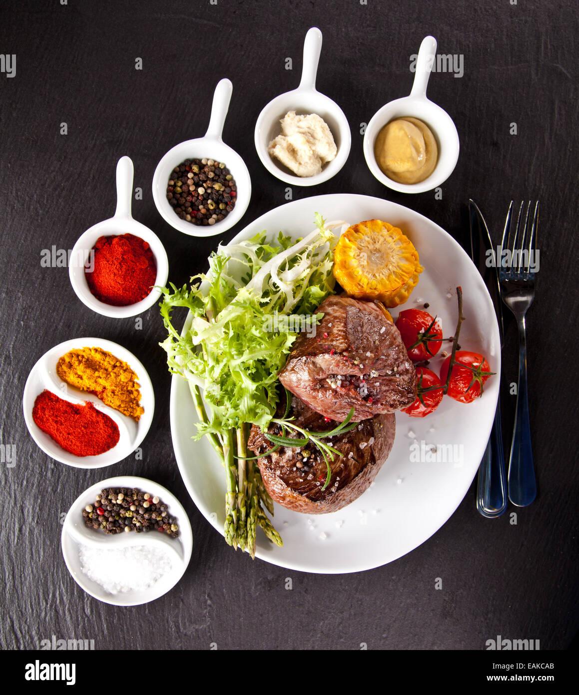 Pezzo di carne rossa di manzo con verdure, erbe e spezie, servito su pietra nera superficie. Scattato dalla vista Immagini Stock