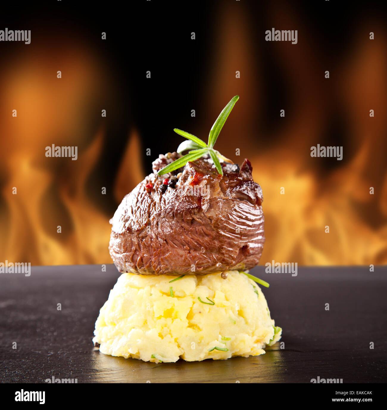 Pezzo di carne rossa di manzo con polenta di patate e rosmarino servita sulla pietra nera superficie. Blur fiamme Immagini Stock