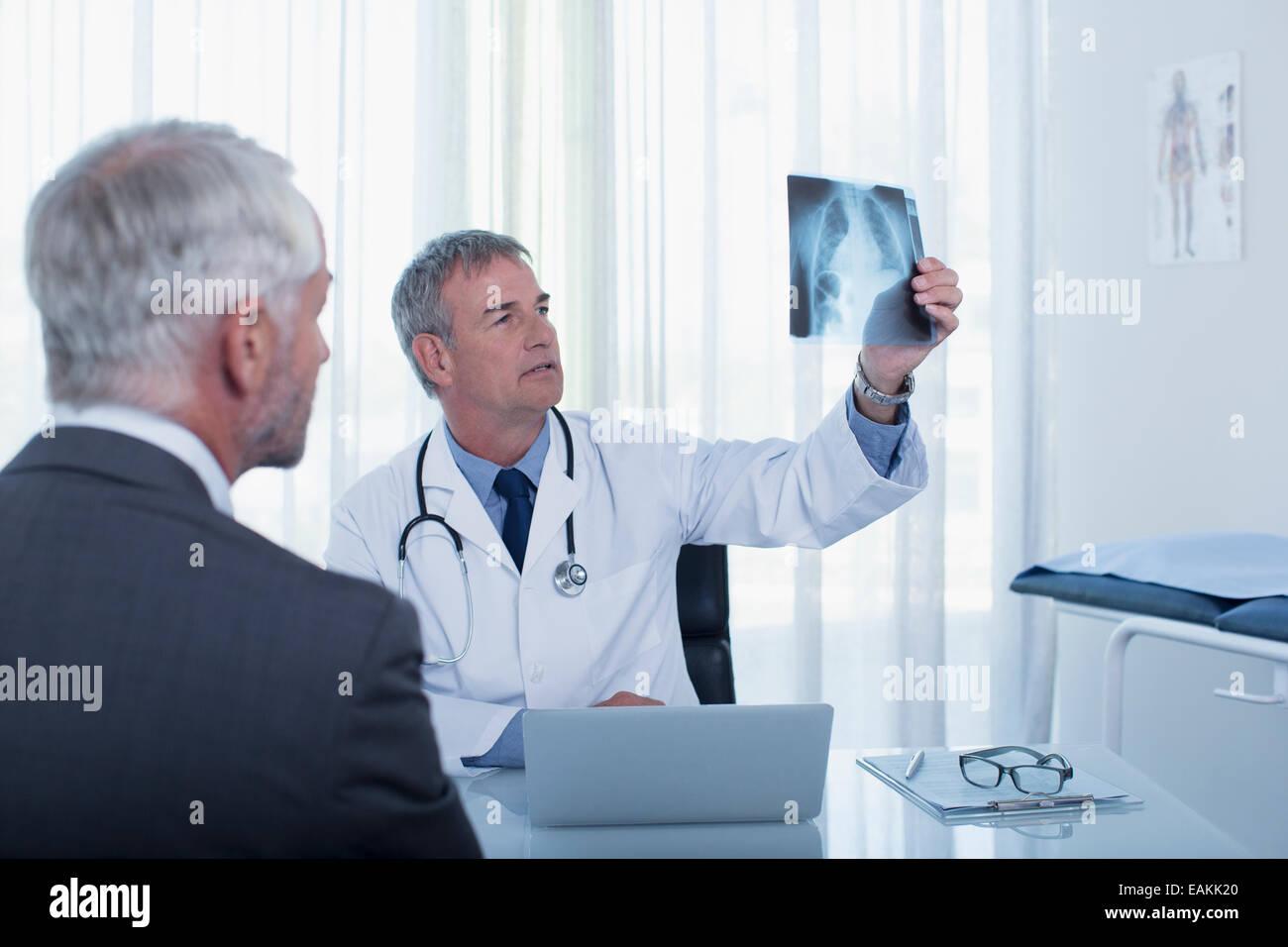 Medico seduto alla scrivania in ufficio l'esame del paziente x-ray Immagini Stock