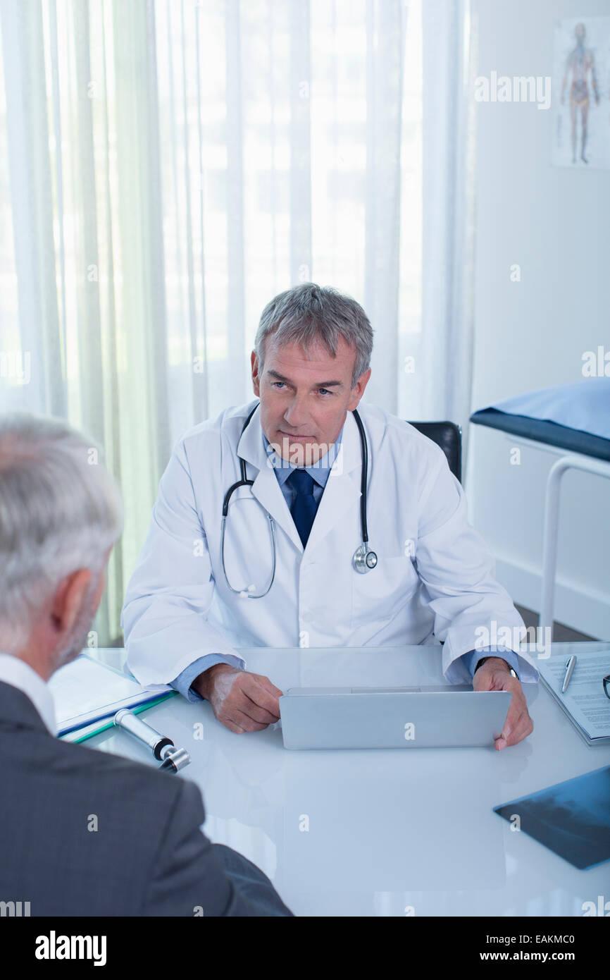 Coppia medico con laptop e uomo seduto alla scrivania in ufficio Immagini Stock