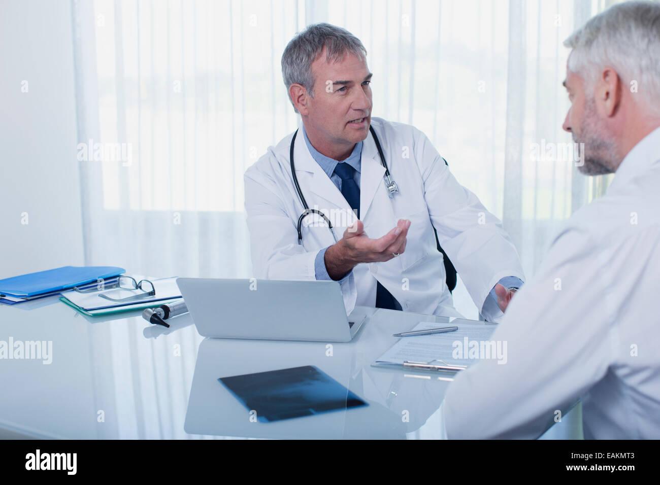 Coppia medico parlando al paziente alla scrivania in ufficio Immagini Stock