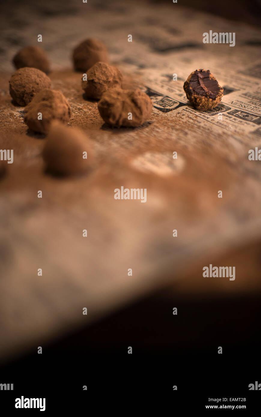 Righe di tartufi di cioccolato ricoperto di cacao su giornali antichi e legno rustico superficie. Un tartufo addentata. Immagini Stock