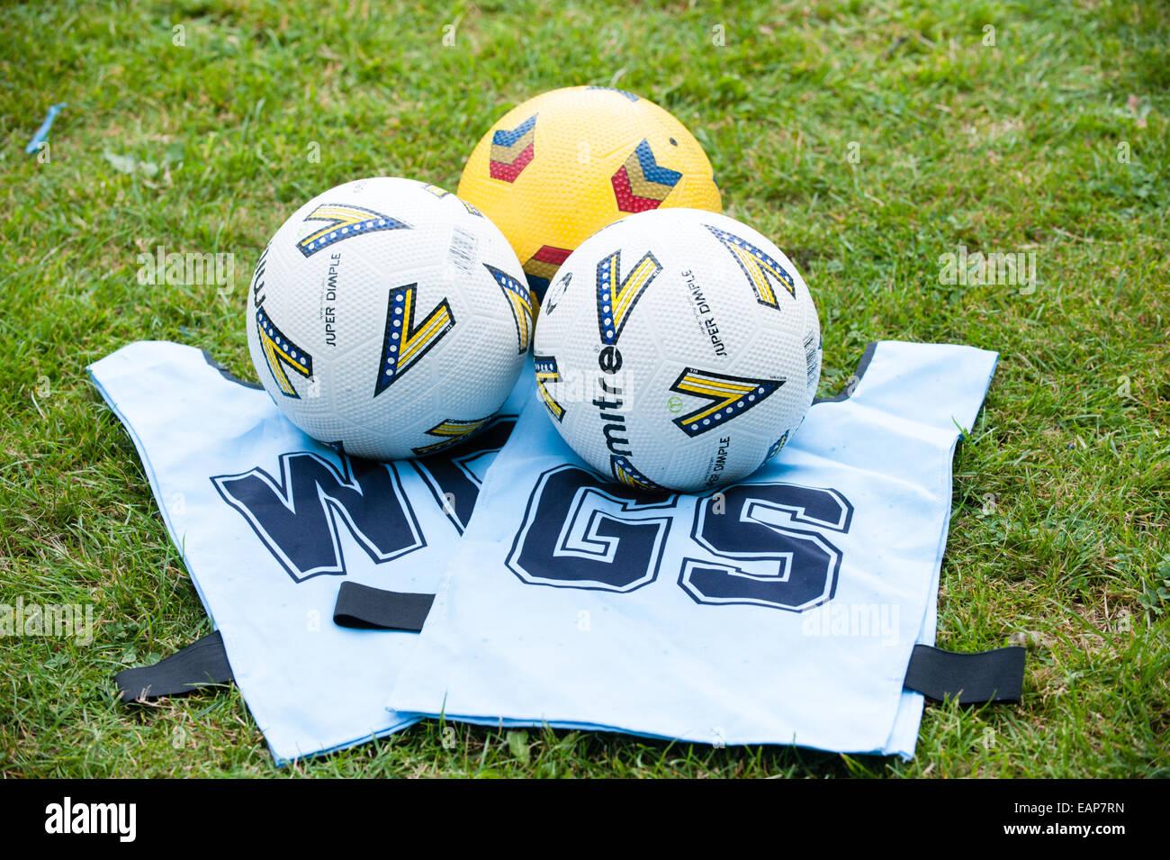 Pulire white netball tabards e tre sfere di netball sull'erba a una scuola corso di coaching Immagini Stock