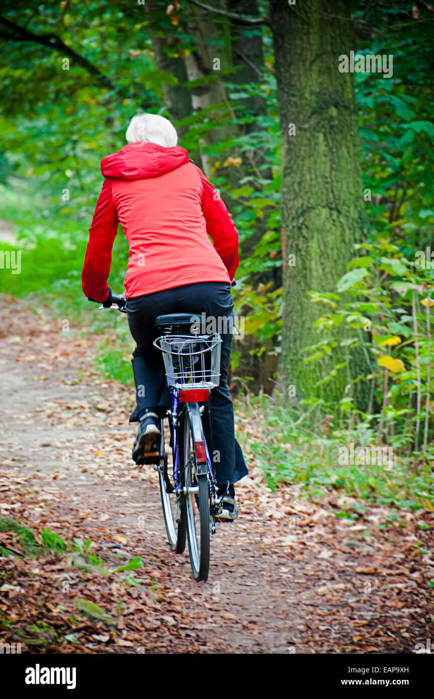 Woman in Red giacca a vento in sella ad una bicicletta in natura Foto Stock