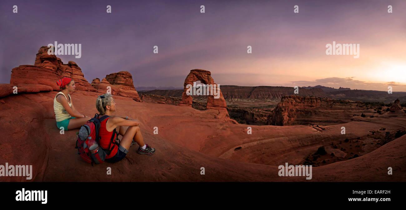 Gli escursionisti seduta a Delicate Arch pietra naturale arch al crepuscolo, Arches-Nationalpark, vicino a Moab, Foto Stock