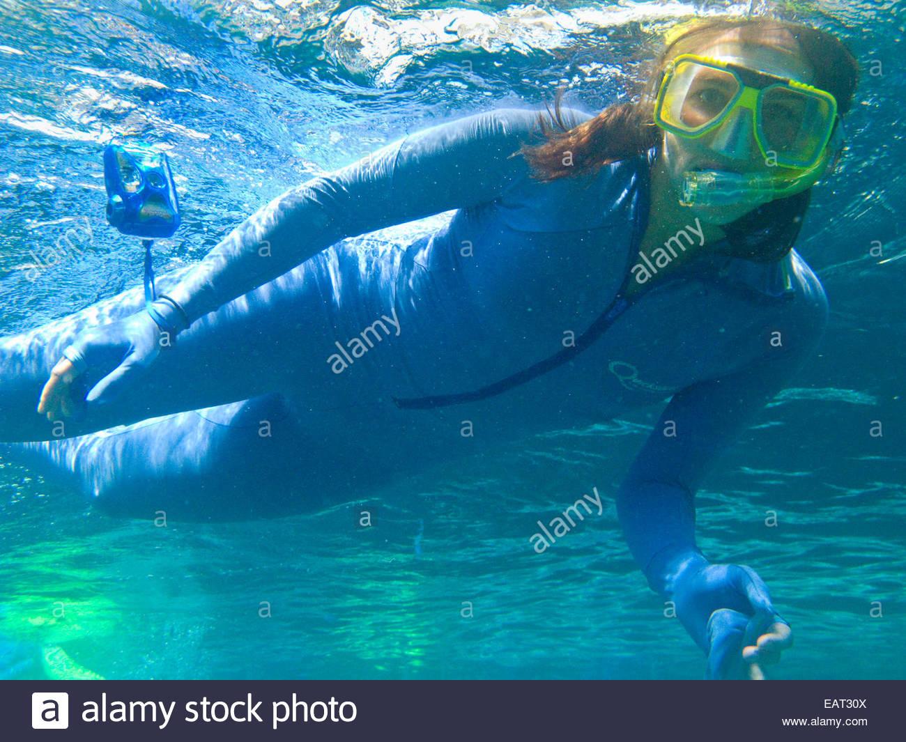 Una donna snorkeler appena al di sotto della superficie. Immagini Stock