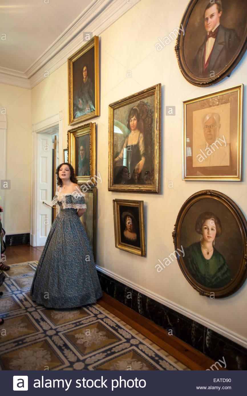 Un museo di docente nel periodo abbigliamento sorge in un corridoio appeso con ritratti di ex Oak Alley Plantation Immagini Stock