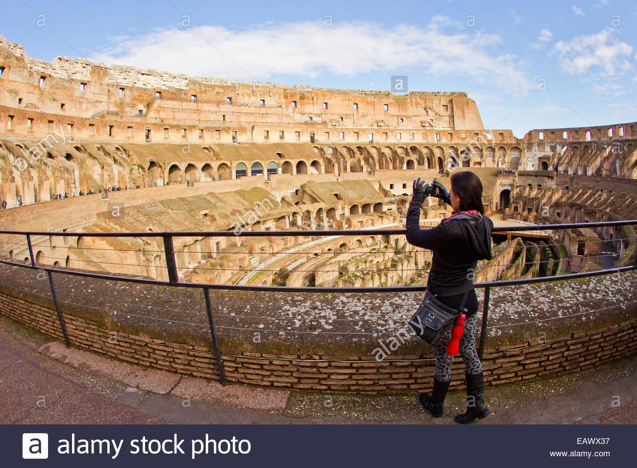 Una donna prende le foto all'interno dell'antico Colosseo romano. Foto Stock
