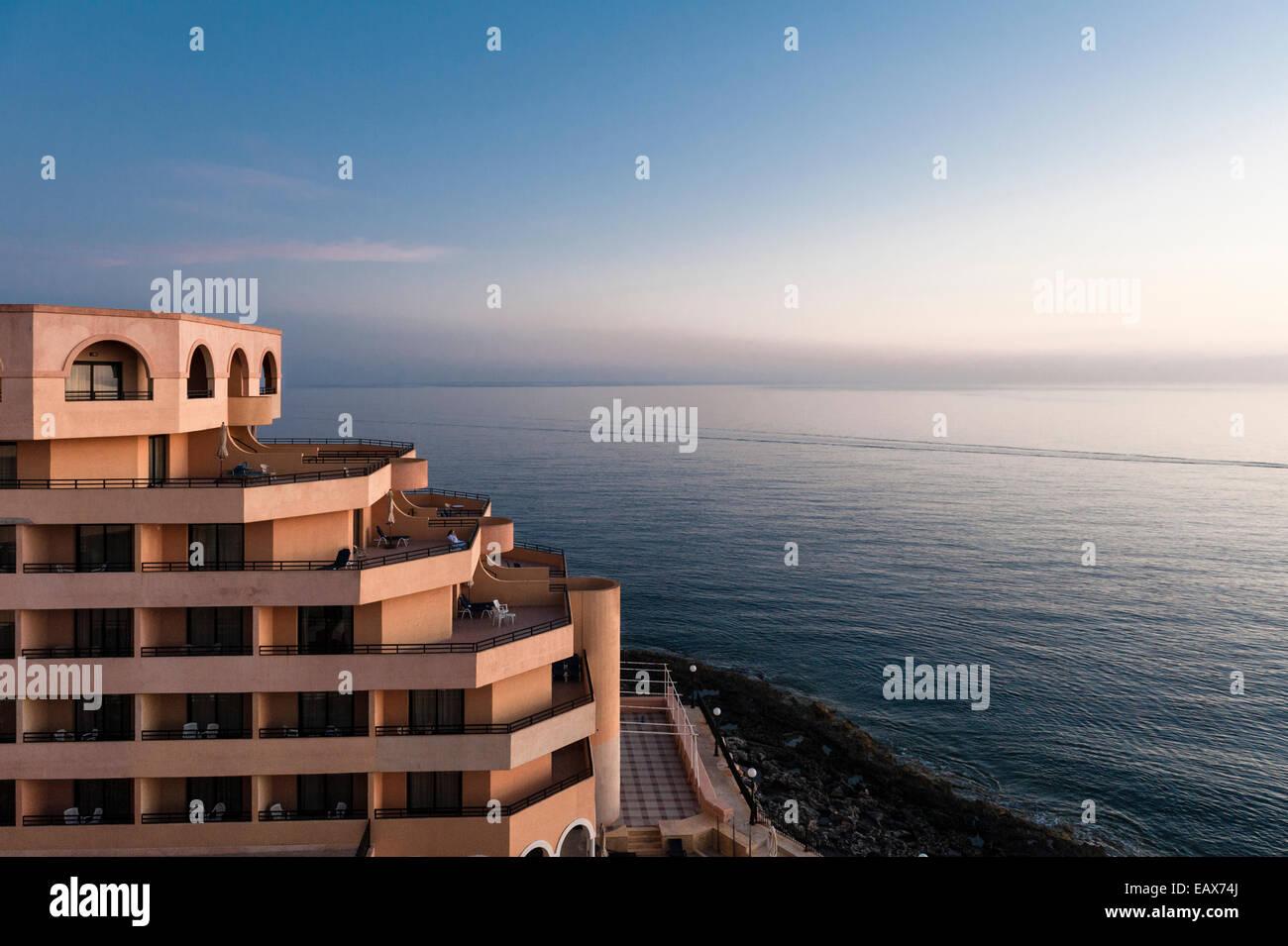 Radisson Blu Hotel, St Julians, Malta. All'alba, una solitaria donna orologi guest il tramonto sul mare Mediterraneo Immagini Stock