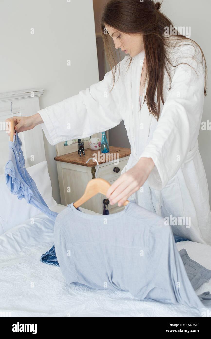 Donna scegliendo camicetta da indossare Immagini Stock