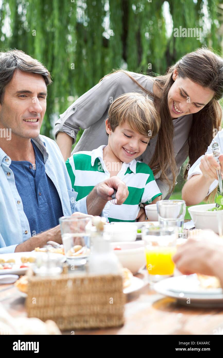 Famiglia mangiare insieme alla raccolta esterna Immagini Stock