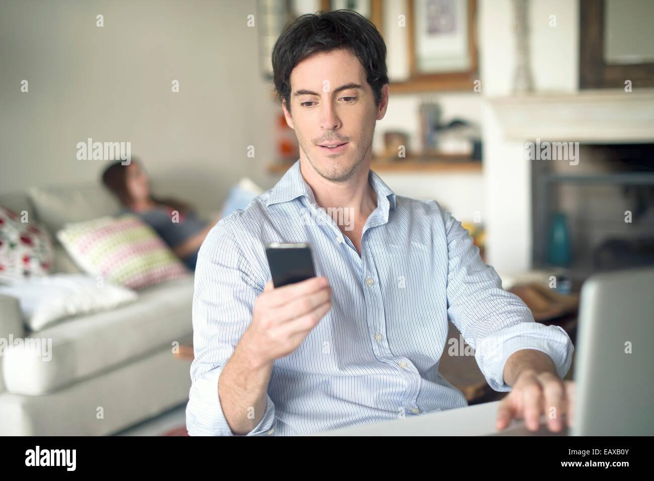 Uomo che guarda un telefono cellulare Immagini Stock