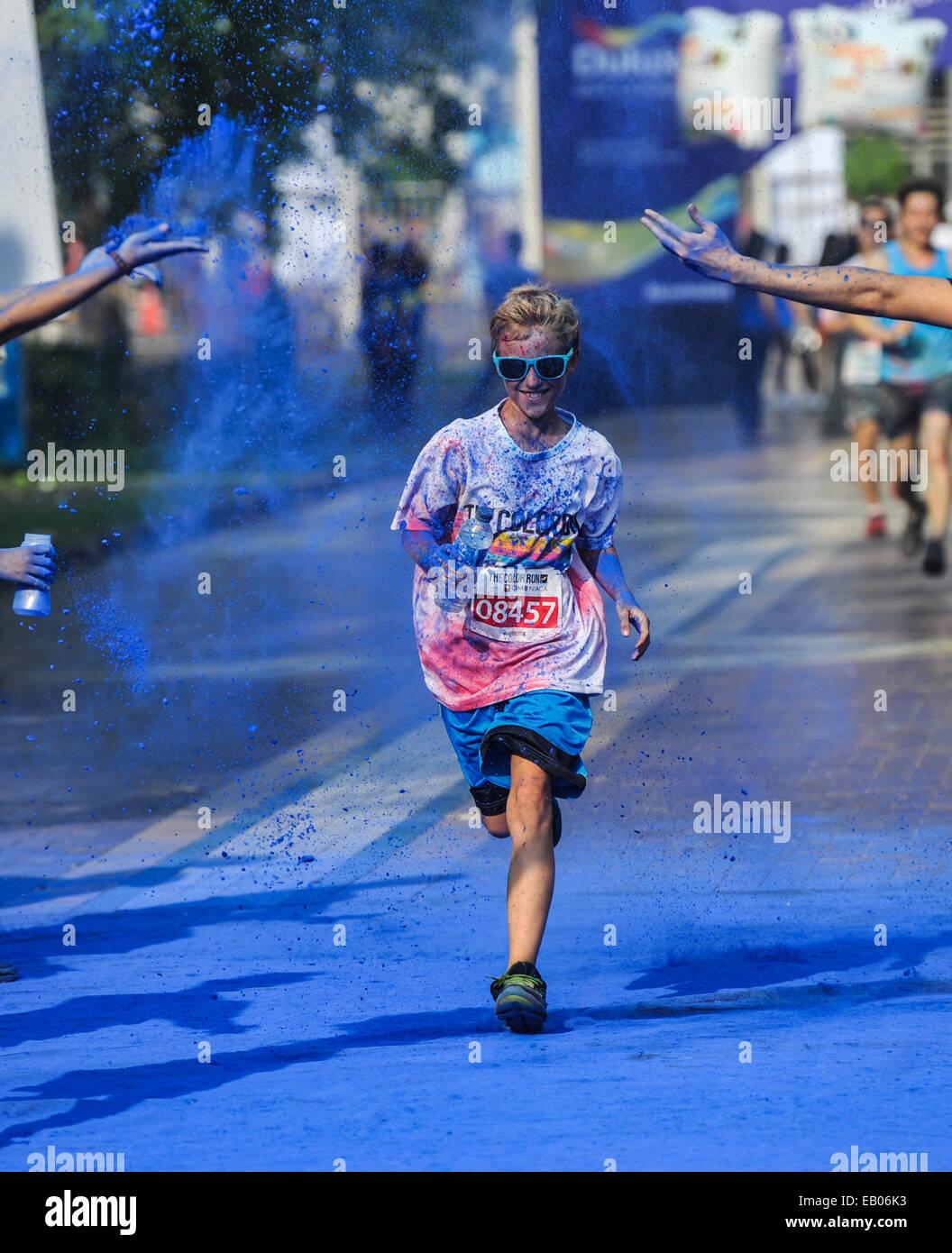 Jakarta, Indonesia. 23 Nov, 2014. Un runner è irrorato da polveri di colore durante un colore eseguire event Immagini Stock