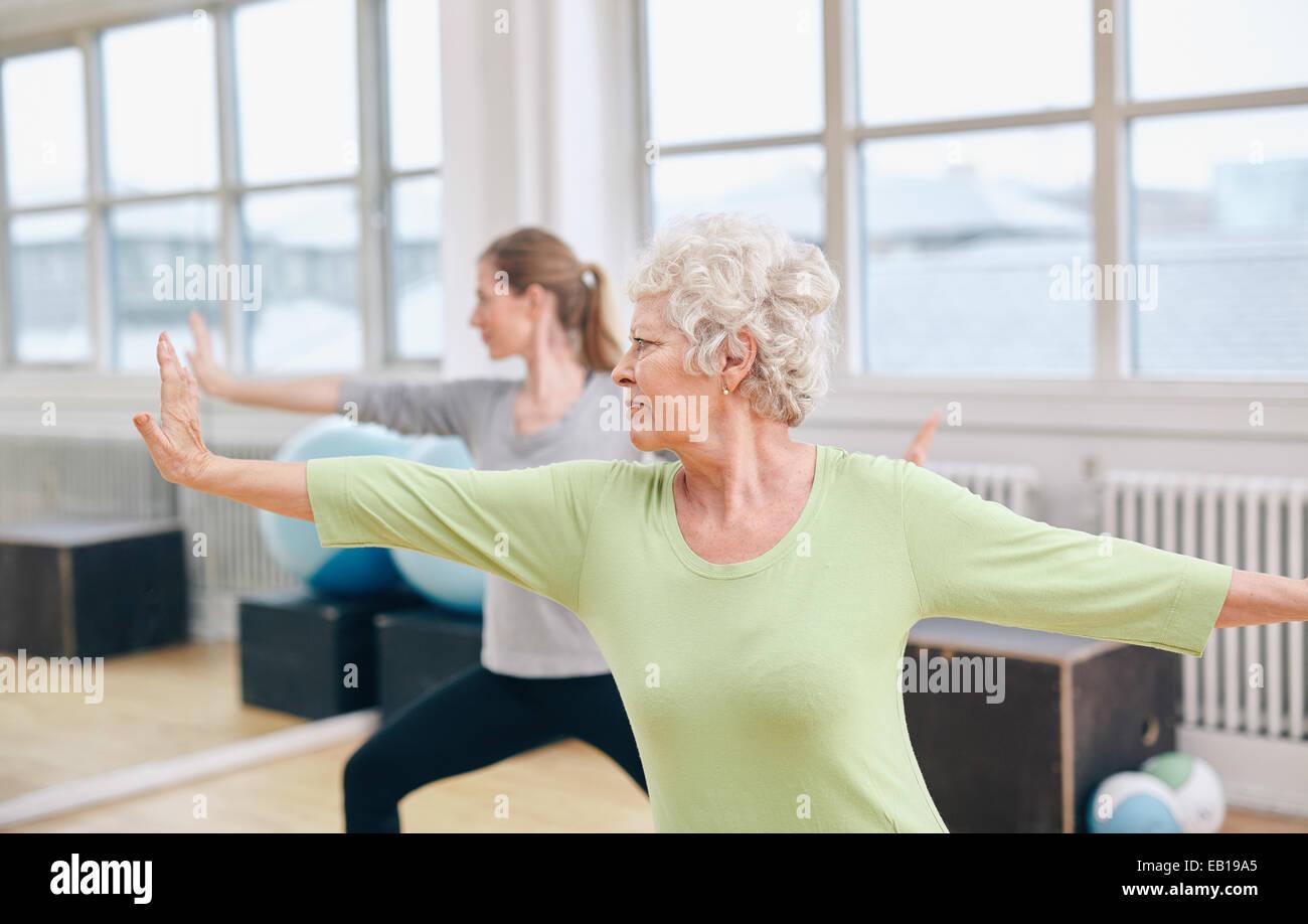 Due donne facendo stretching e yoga allenamento in palestra. Trainer femmina in background con il senior donna di Foto Stock