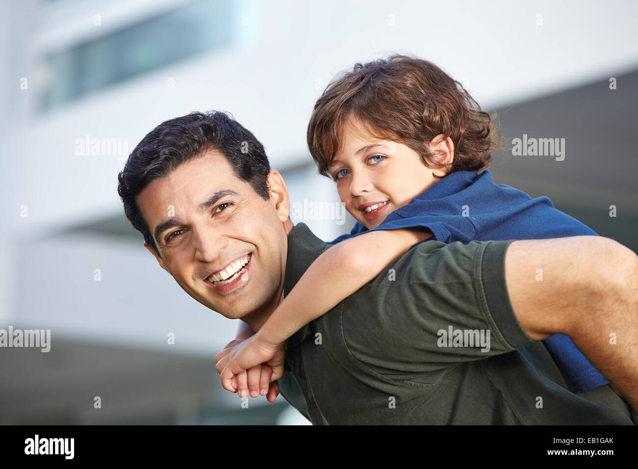 Bambino felice a cavallo trasportato su suo padre sorridente Immagini Stock