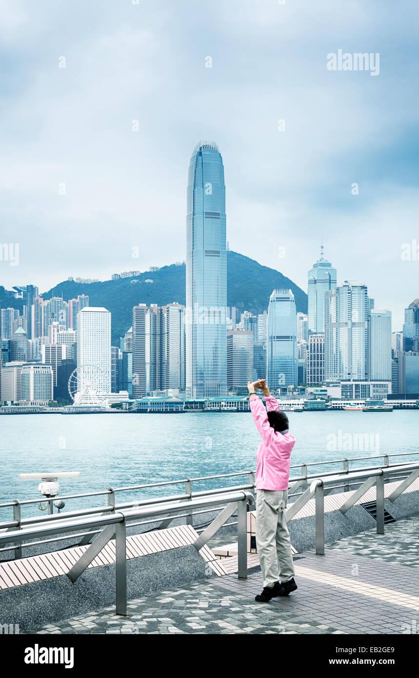 Ginnastica mattutina a Kowloon molo pubblico con una vista del centro finanziario internazionale. Immagini Stock