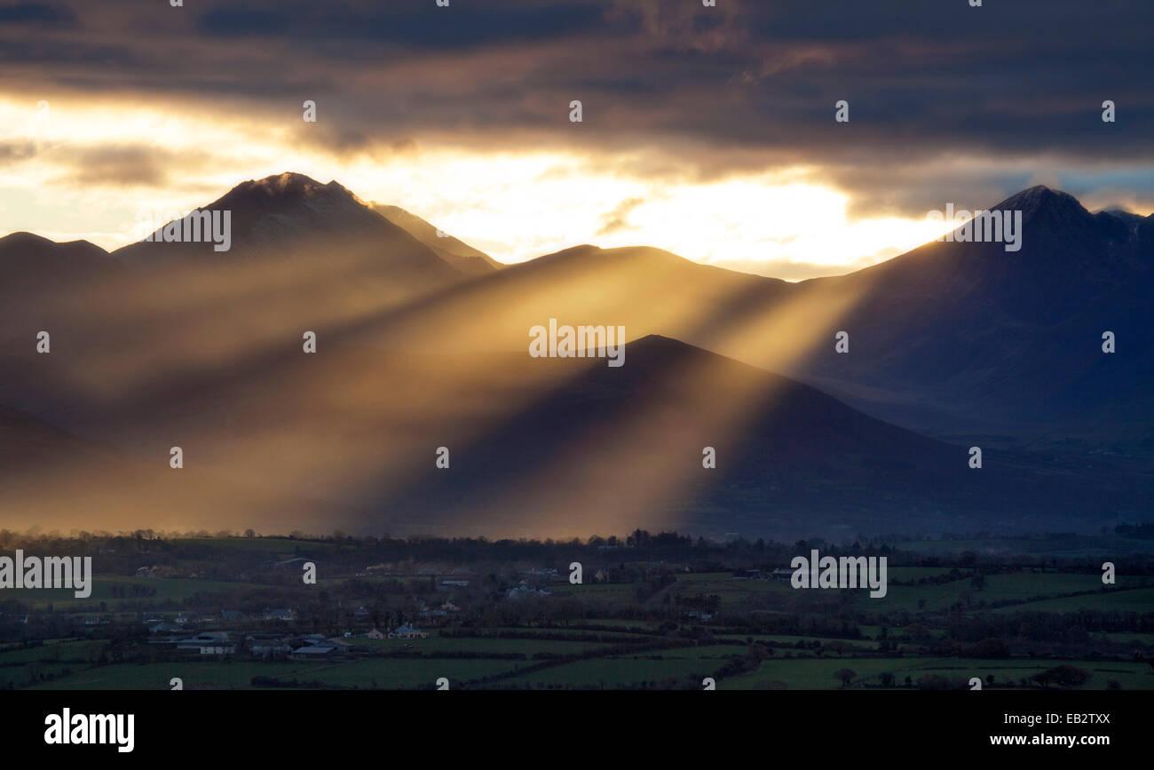 Raggi crepuscolari oltre Carrauntoohil e dell'Macgillycuddy Reeks, nella contea di Kerry, Irlanda. Foto Stock