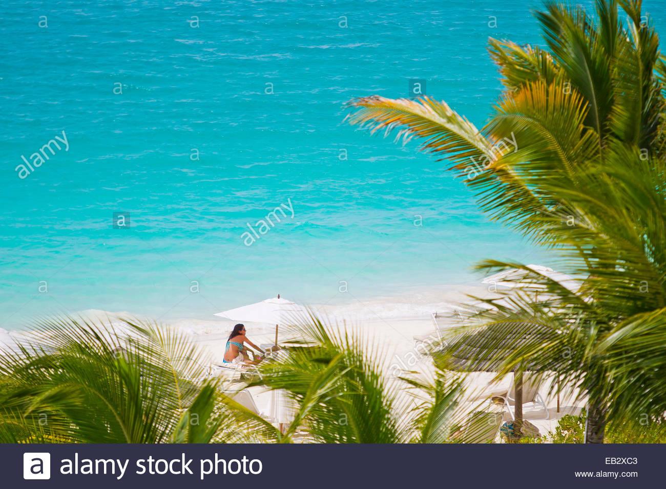 Una giovane donna relax su una spiaggia tropicale appena al di là di palme che soffia in una brezza. Immagini Stock