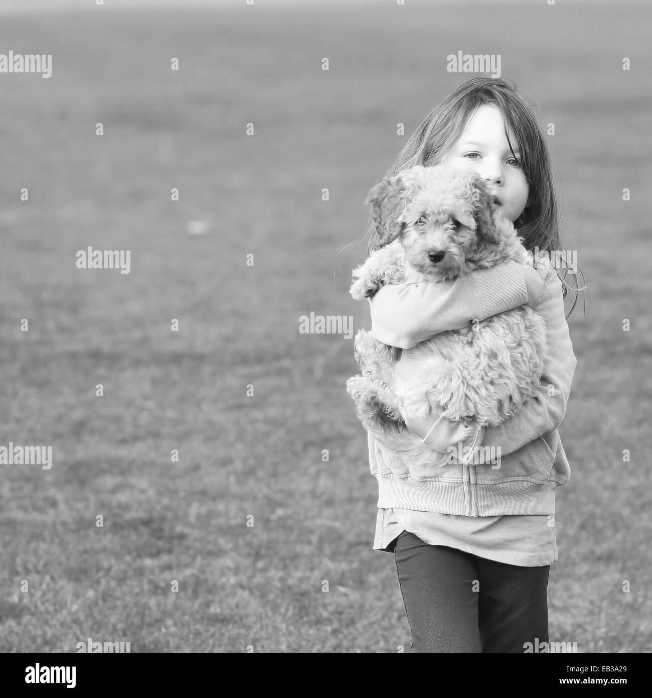 Ragazza che trasportano cucciolo di cane Immagini Stock