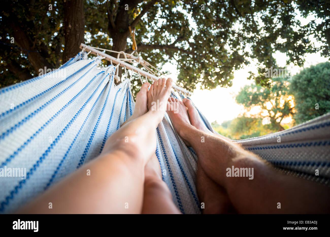 Giovane rilassante in amaca sotto agli alberi Immagini Stock