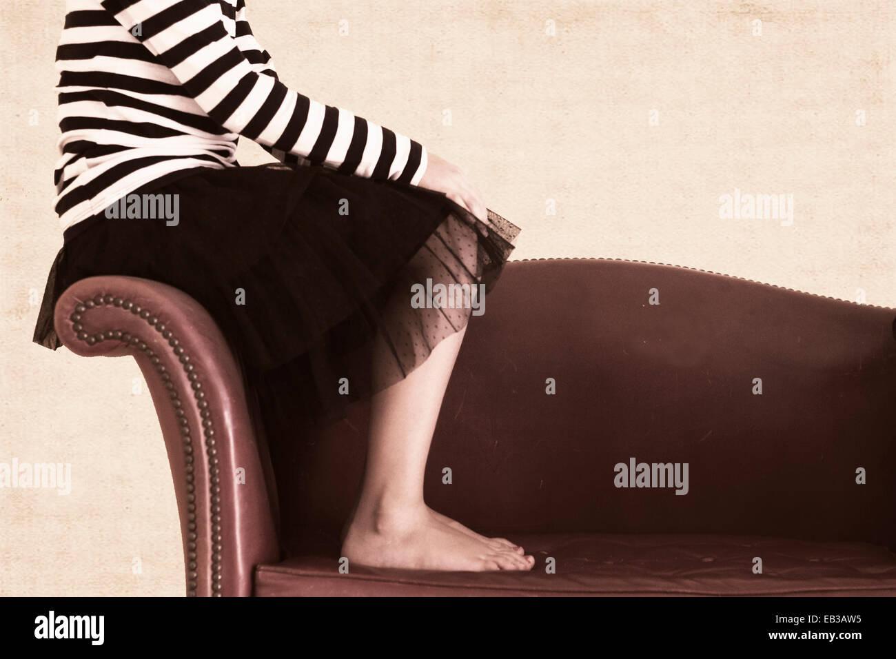 La ragazza (6-7) seduto sul braccio del divano Immagini Stock