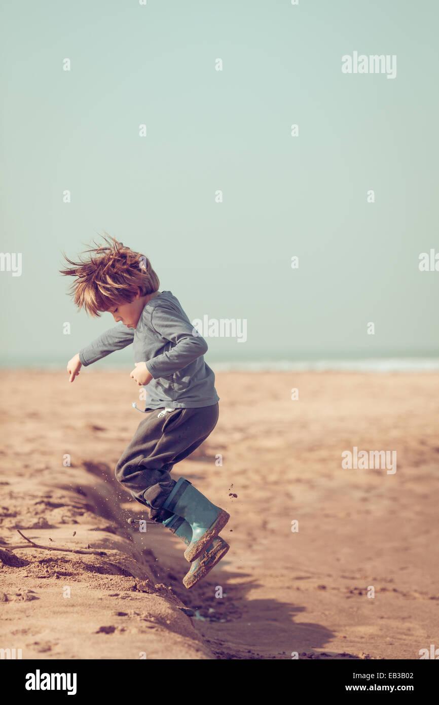 Ragazzo saltando in sabbia sulla spiaggia, Marocco Immagini Stock