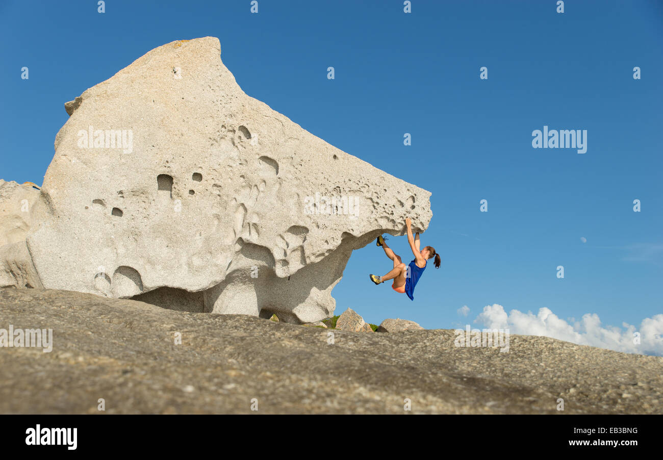 Francia, Corsica, Donna salendo sulla grande roccia singolo Immagini Stock