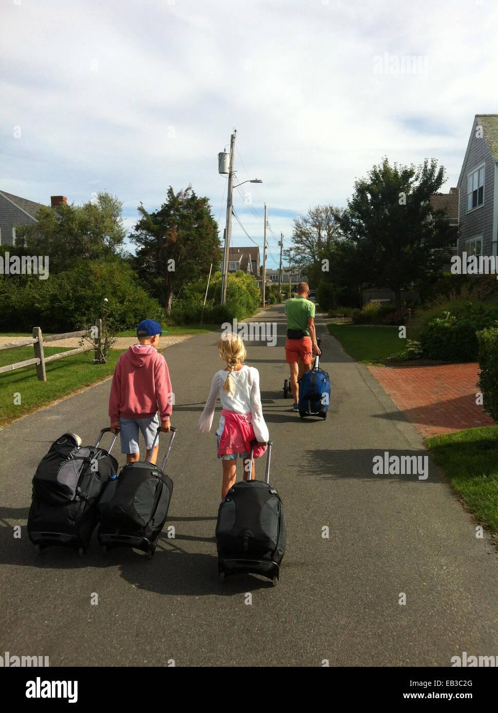Padre di due figli camminando per strada tirando le valigie Immagini Stock