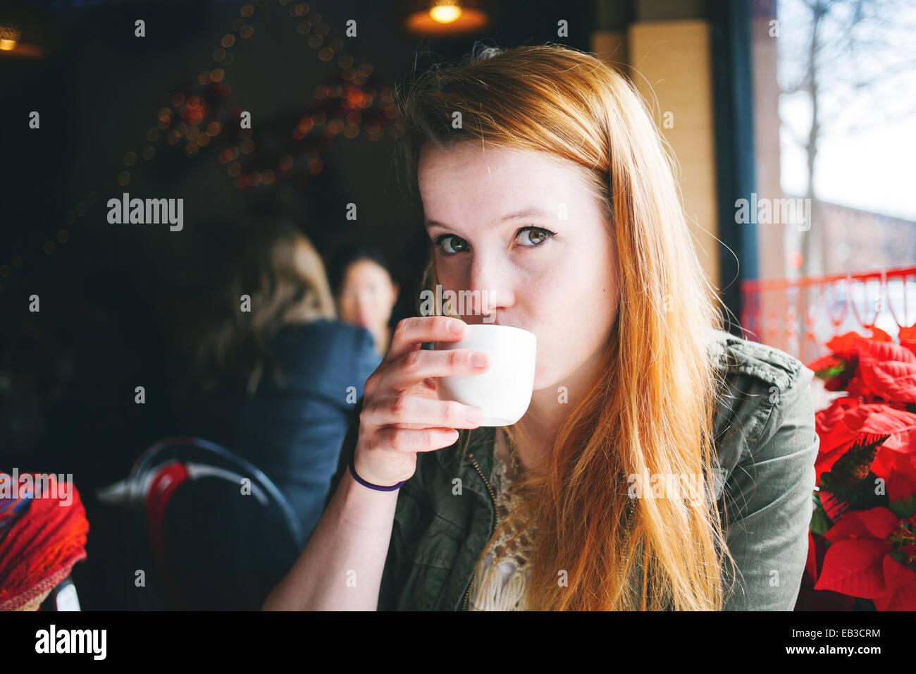 Stati Uniti d'America, Illinois, Chicago, Ritratto di giovane donna sorseggiando dalla tazza bianca in ristorante Immagini Stock