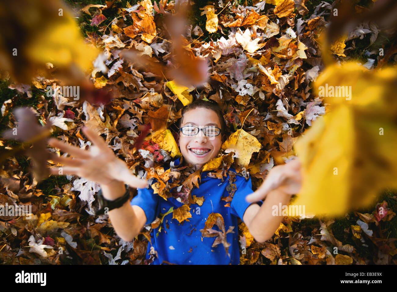 Stati Uniti d'America, Maryland, Howard County, Dayton, ragazzo recante sul retro e giocando con le foglie di Immagini Stock