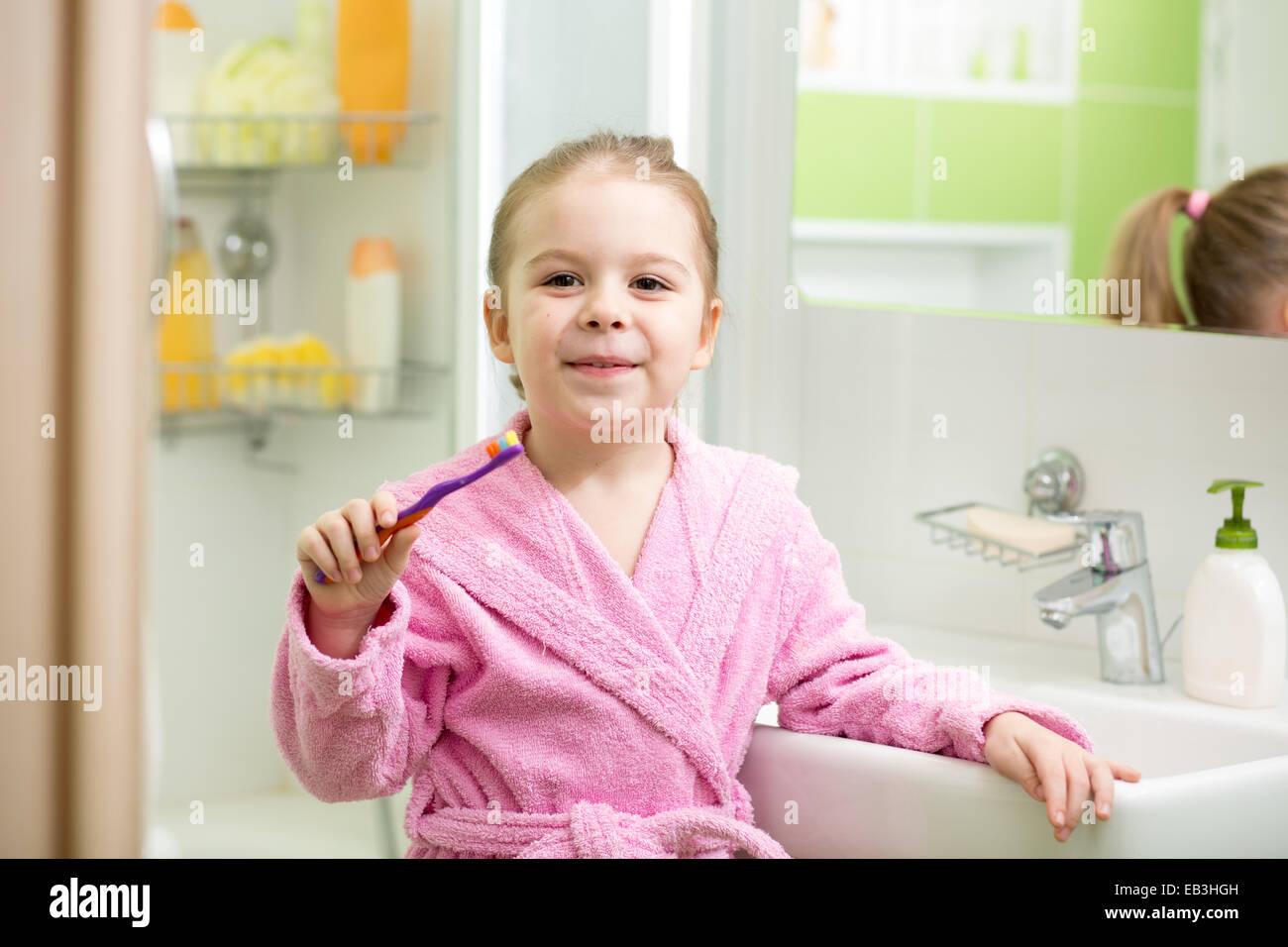 Kid girl spazzolare i denti in bagno Immagini Stock
