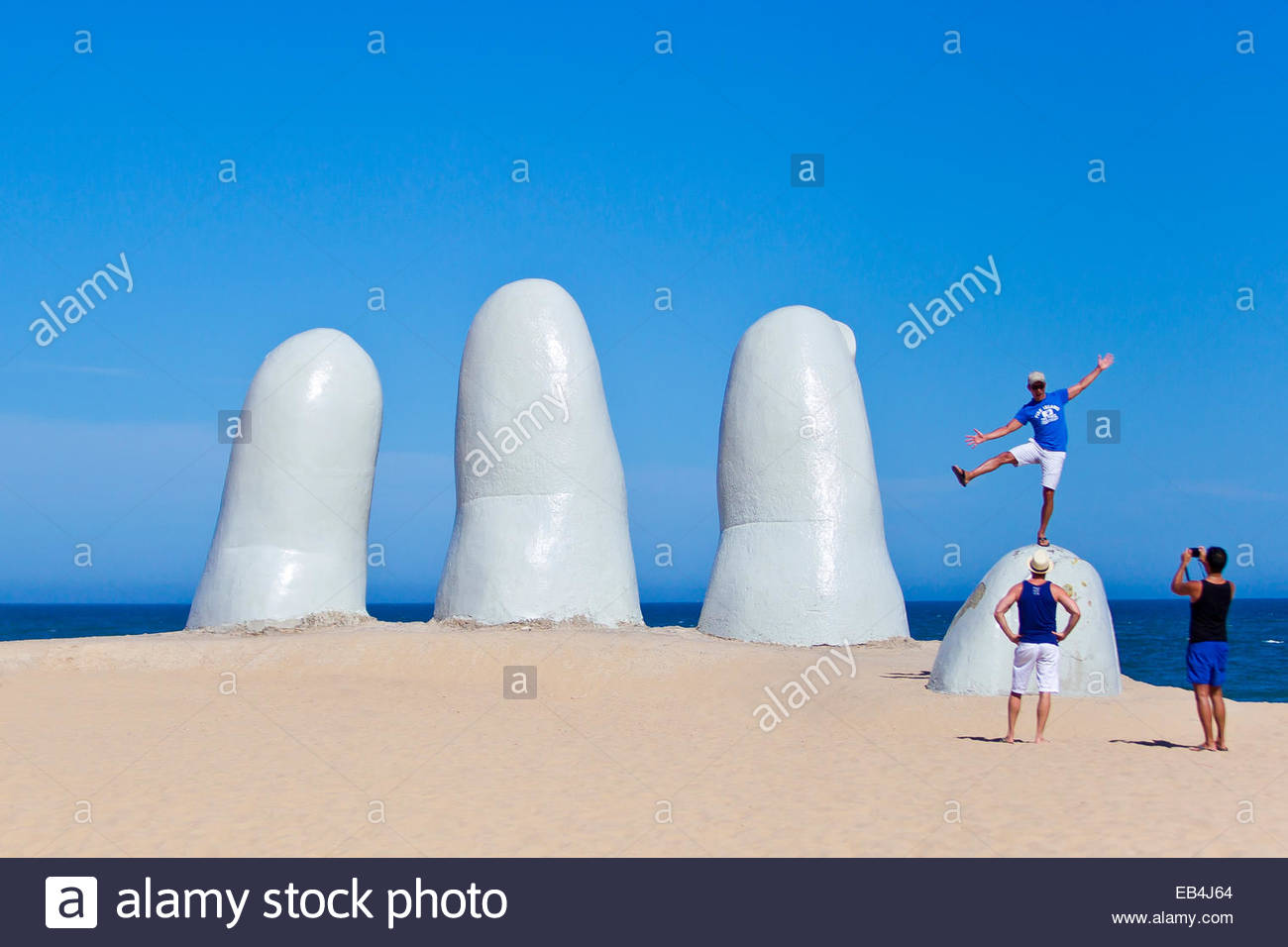 Spiaggia-frequentatori e turisti ad esplorare la mano o mano de Punta del Este, creato nel 1982 dal pittore cileno Immagini Stock