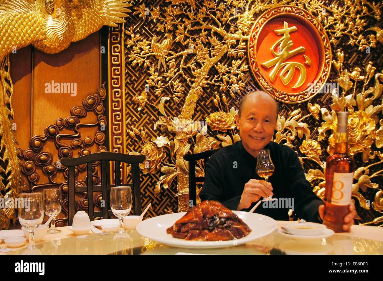 Proprietario del famoso Ying Kee ristorante dal 1942 Tariquet potabile armagnac con l'anatra arrosto Lan Kwai Immagini Stock