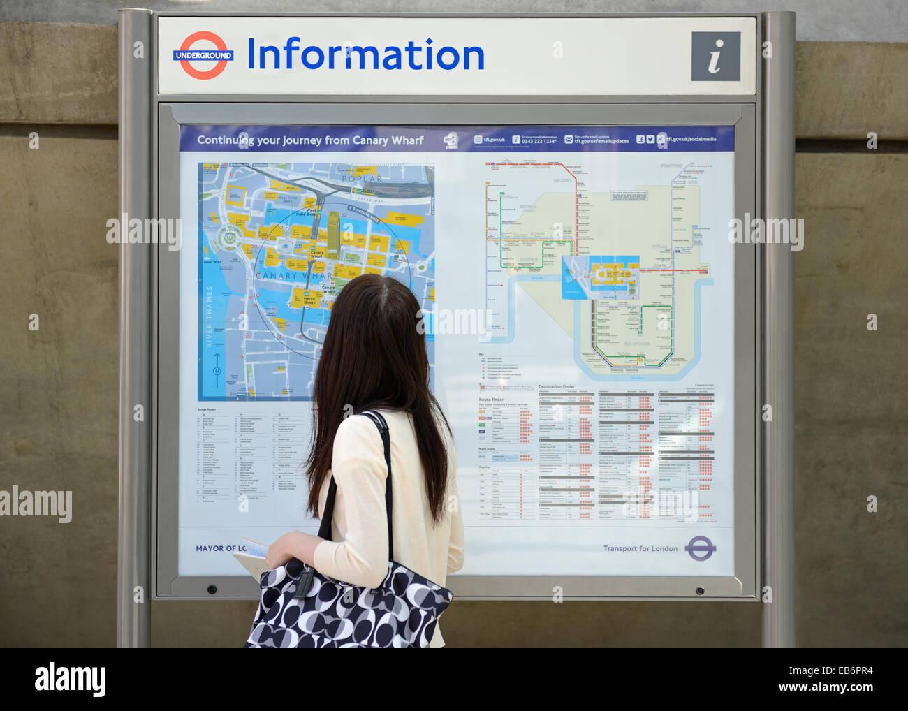 Donna che guarda la mappa di una città con Informazioni di viaggio, Canary Wharf, London, Regno Unito. Immagini Stock