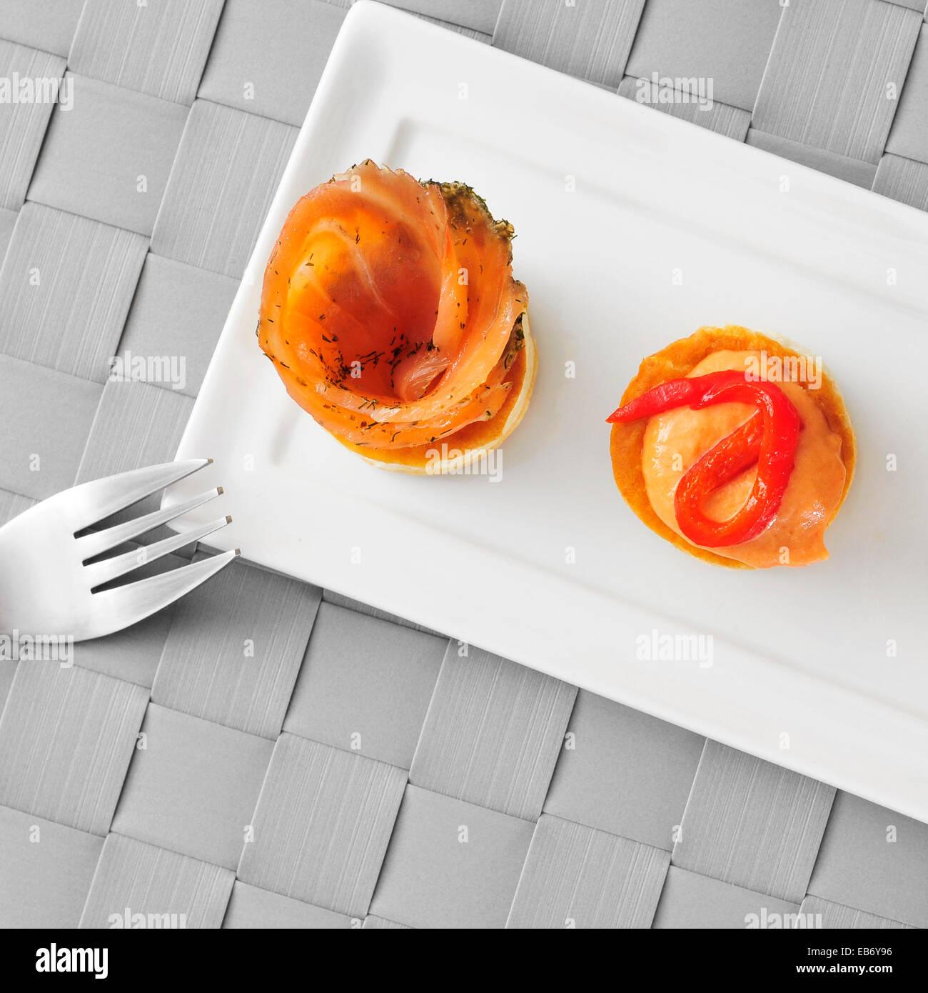 Una piastra con alcune diverse volauvents, uno riempito con salmone affumicato e l'altra uno riempito con pepe Immagini Stock