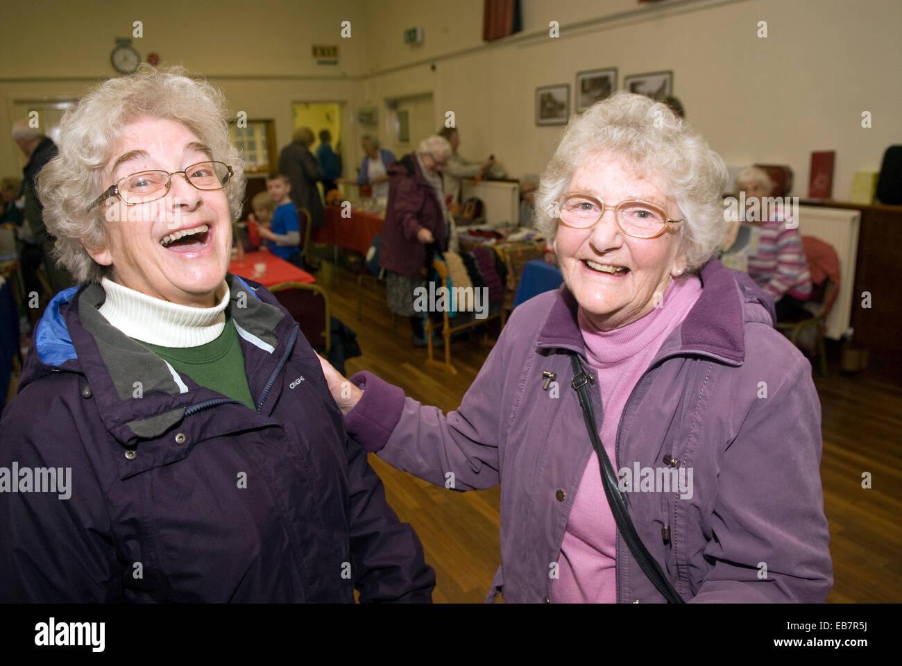 Smiley due anziane signore a natale il mercato coperto, liphook, hampshire, Regno Unito. Foto Stock