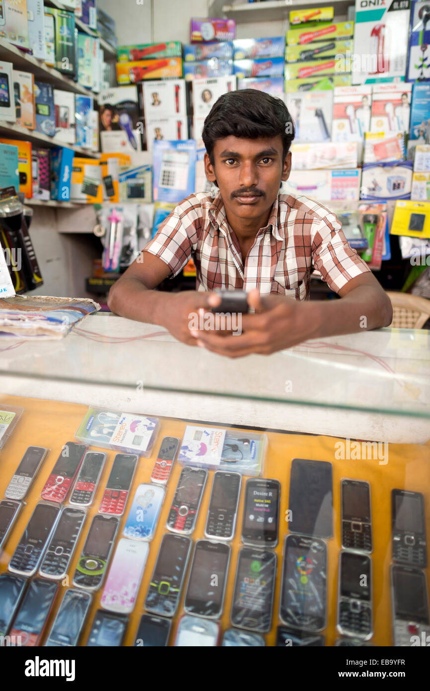 Telefono cellulare del venditore nel suo negozio, Madurai, Tamil Nadu, India Immagini Stock