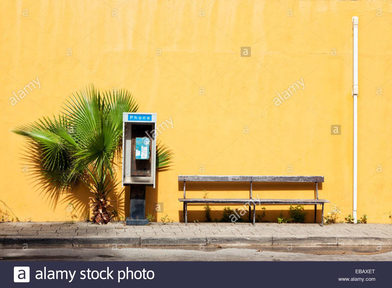Rotture di cabina telefonica, Palm tree e bancone di orange parete dipinta, Willemstad, Curaçao Immagini Stock