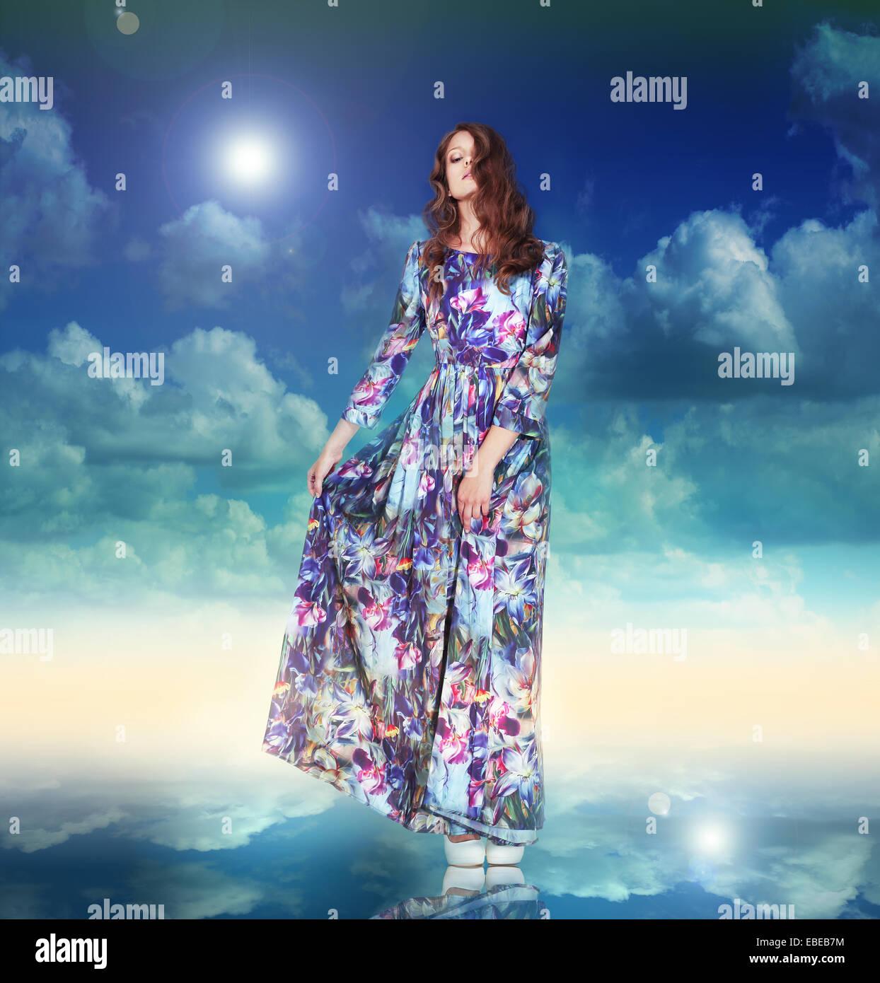 La fantasia. Donna in abito leggero è in bilico tra le nuvole Immagini Stock