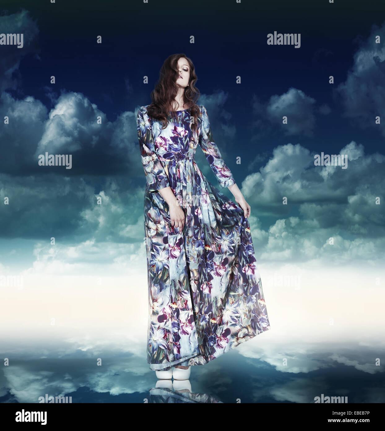 La fantasia. Donna di lusso in abito variegato oltre il cielo blu Immagini Stock