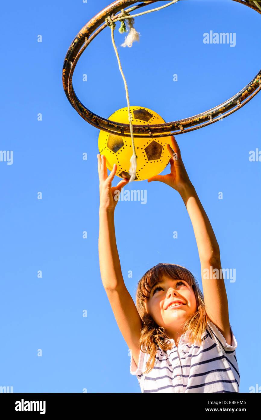 7 anno vecchia ragazza giocare a basket Immagini Stock