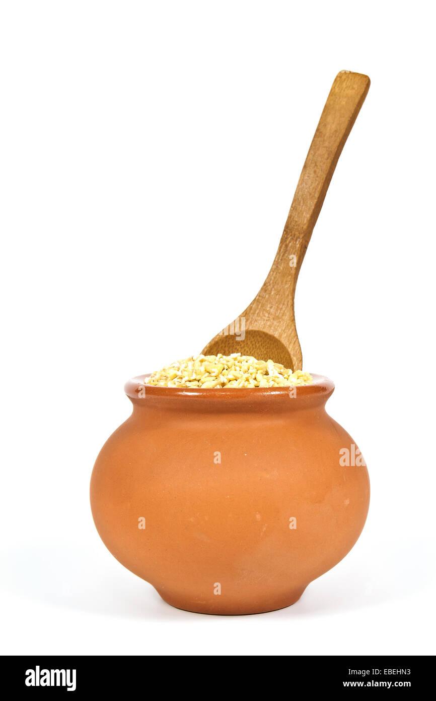 Manna groppa in una pentola di creta con un cucchiaio di legno su sfondo bianco Immagini Stock