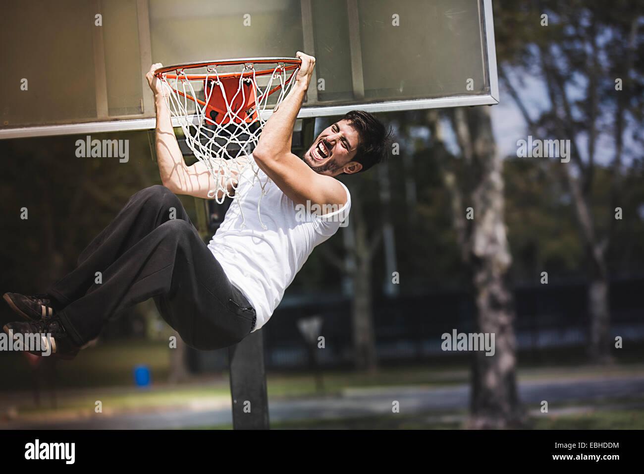 Giovane maschio basket appesi da Basketball hoop Immagini Stock