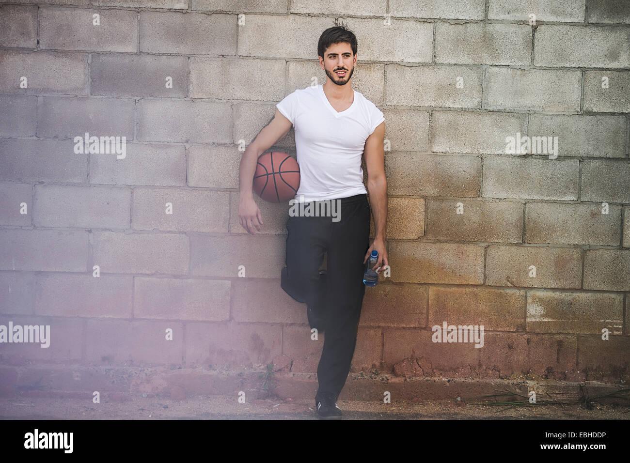 Maschio giovane giocatore di basket appoggiata contro la parete Immagini Stock