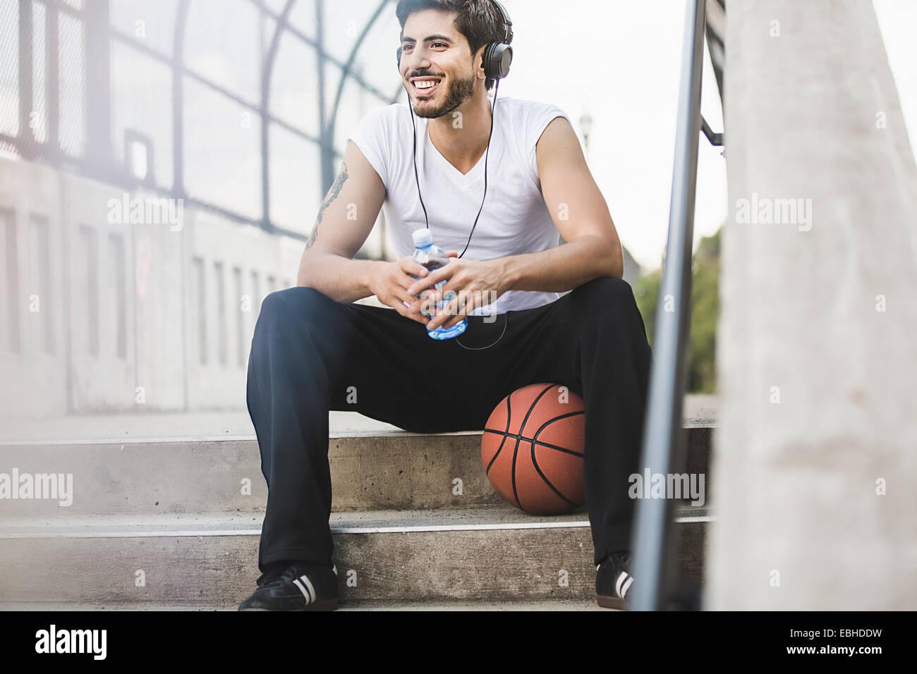 Giovane maschio basket giocatore seduto su passerella ascoltando le cuffie Immagini Stock