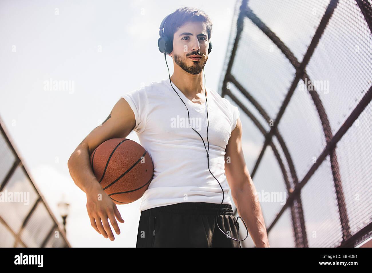 Maschio giovane giocatore di basket a camminare lungo la passerella ascoltando le cuffie Immagini Stock